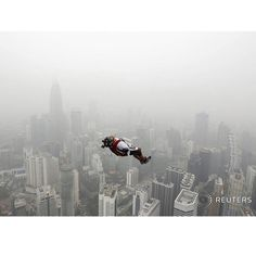 A BASE jumper leaps from the 300-metre high Kuala Lumpur Tower during the International Tower Jump in which more than 100 people take part on a hazy day in Kuala Lumpur Malaysia October 2 2015. Slash-and-burn agriculture in neighbouring Indonesia has blanketed Malaysia and Singapore in a choking haze for weeks. REUTERS/Olivia Harris  #malaysia #basejump #height #vertigo #kualalumpur #Asia by reuters