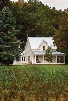 Classic farmhouse: white board-and-batten with a tin roof and wide porch.