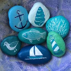 This collection of painted rocks would look great in a beach house - or it could remind you of the sea once youre home again.  I painted the rocks in shades of blue, turquoise, aqua and mint green and then drew sea and beach themed images on them. Each rock is signed by me underneath and then varnished.  The rocks vary in length from 1 3/4 inches to nearly 3 inches (4.5 to 7.5 cm).  They will ship individually wrapped inside a padded envelope.