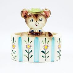 A baby mouse (or perhaps a baby bear) is peeking out of an oval shaped planter.  The base has blue and white stripes with flowers and there is a rhinestone accent on the front. Super cute vintage pre-owned collectible glazed porcelain ceramic flower planter that was originally used to hold floral arrangements or plants but could be easily re-purposed to hold various items in the nursery, upcycled to a desk or dresser caddy for small objects, or just a great addition to a planter collection.