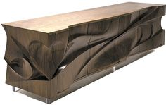 """This dynamic cabinet/sculpture is made from beautiful exotic hardwood. Deep carved wood exterior and sides form undulating lines, sunken nooks and crevices to create a formidable facade. The unit rests on a 4"""" high Plexiglas base and has four adjustable shelves."""