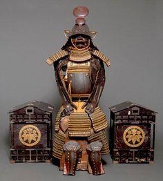 Imposante armure de guerrier japonais (yoroi) avec deux rares coffres de rangement. L'armure comprend.: des cordelettes de couleur orange, un casque kabuto, un masque facial (menpo) figurant une bouche grande ouverte, un protègegorge, une cuirasse noire et des protections pour le bas des jambes. Vendu aux #encheres 15000€ par Boisgirard Antonini le 20/11/13
