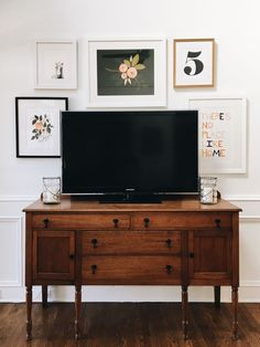 That wooden sideboard below the television + gallery wall around the TV!! Click through to see more of this lovely room!