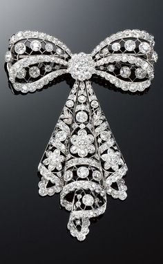 DIAMOND BROOCH, 1910s. In the garland style, designed as an articulated tied ribbon decorated with stylised floral motifs millegrain- and collet-set with circular- and single-cut diamonds.