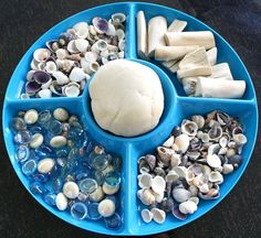 "Invitation to play with coconut scented play dough, shells, glass beads & small pieces of drift wood ("",)"