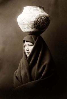 You are viewing an unusual image of En Al Leih, an Indian Woman. It was taken in 1903 by Edward S. Curtis.    The image shows the Indian woman in a half-length portrait, facing left, with decorated clay pot on head.    We have created this collection of pictures primarily to serve as an easy to access educational tool. Contact curator@old-picture.com.    Image ID# 5A95374B