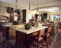 Luxury kitchen with two islands, eat-in bar, stainless steel appliances, and high end furnishings.