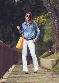 Shop this look for $302:  http://lookastic.com/women/looks/button-down-shirt-and-belt-and-tote-bag-and-jeans-and-pumps-and-bracelet/3156  — Blue Chambray Button Down Shirt  — Black Leather Belt  — Mustard Leather Tote Bag  — White Jeans  — Brown Suede Pumps  — Gold Statement Bracelet