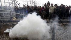 Macedonian police fired tear gas and stun grenades Monday as several hundred Iraqi and Syrian refugees, frustrated at days of delays in crossing the Greek-Macedonian border, broke down a gate at a nearby rail crossing.