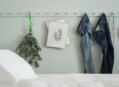 Jeansbroeken, gedroogde planten en kunstwerken hangen aan haken die in dezelfde lichtgroene kleur als de wand zijn geschilderd