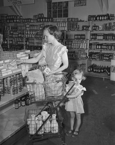 A mother and daughter in matching ruffled pinafore dresses shopping at a Los Alamos supermarket, 1940s