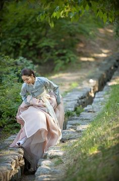 Woman wearing hanbok in beautiful korean garden