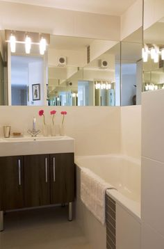 transforming a small bathroom. mirrors wrapped around the room make it seem bigger, fancier look too