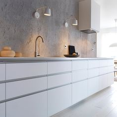 Modern white IKEA kitchen with white worktops, white wall-mounted fan
