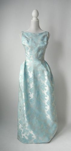 Vintage 1950s light blue satin damask gown. Fully lined in blue rayon with a back metal zipper, there is tulle in the skirt for fullness at the hips. Made in Toronto by Marie Cluthé. Size: small, US 4