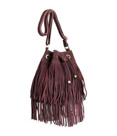 Burgundy red, suede bucket bag with fringe & gold-tone hardware. Adjustable shoulder strap & drawstring closure. | H&M Accessories