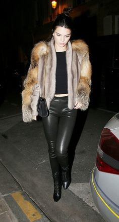 Kendall Jenner wears a crop top, cropped fur coat, leather leggings, and lace-up ankle boots