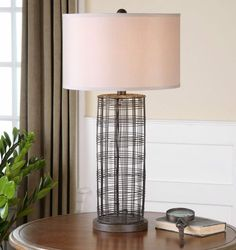 Hand-forged metal cylinder base with a rustic bronze finish. #uttermost