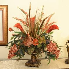 "Silk Floral Centerpiece with Calla Lillies, Peonies, Orchid& Feathers AR317. tail feathers and terra cotta silk flowers come to life in a renaissance fluted vase. Calla Lillies, hydrangeas and grasses are also used by our designer in this unique design. Measures 24 H"" x 24"" W x 14"" D #silkflowers"