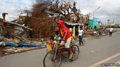 People travel past debris caused by Typhoon Haiyan in Tanauan, Leyte, 16 November
