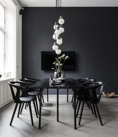 A cascade white pendant lights stands out in this dramatic black minimalist dining area.