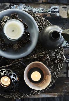 """SINNLIG Duftkerze im Glas mit Duftnote """"Süße Vanille"""" in Naturfarben und Zweige mit Zapfen auf einem gewebten Tischset."""