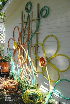 wall art with old hoses.  this would look cute on the side of a shed