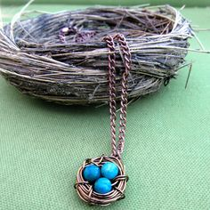 Copper wire wrapped bird nest with multi-colored turquoise and green speckled colored eggs attached to an 18 inch copper colored chain. MEMBER - Wyoming Creative