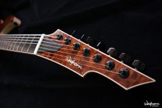 Waghorn corax 7 headstock, with Flamed Maple binding, Walnut veneer purfling, Mother of Pearl logo, body-matching Quilted Maple facing and Schaller M6 locking machines.