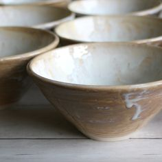 Custom made stoneware pottery bowls in dripping white and ocher glaze.