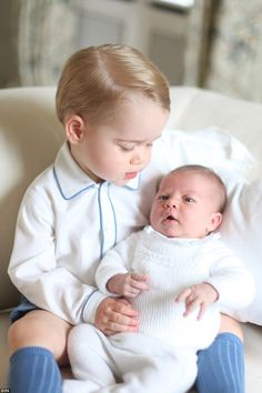 Besotted: In a touching moment the young Prince George, who turns two next month, looks down adoringly at his baby sister Princess Charlotte]