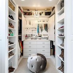Chic walk in closet features a West Elm Large Rectangle Hanging Capiz Chandelier placed over a white closet island fitted with modular shoe shelves topped with white marble. Wooden Drawers, Wooden Cabinets, White Closet, Walk In Closet, Closet Chandelier, Beaded Chandelier, Perfume Storage, Light Wooden Floor, Hat Shelf