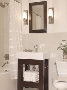 A miniature vanity with a small storage shelf and matching mirror are a perfect fit for this contemporary bathroom. A sheer white curtain and white-tiled walls visually expand the space.