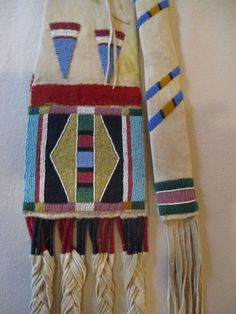 Crow Elk hide pipe bag with attached stem case. Classic sinew and thread beadwork and construction and trimmed with red and green trade stroud and braided hide fringes wrapped with Germantown yarn. Could be a replica?