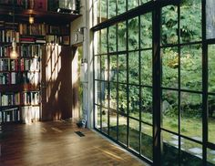 Another room with books completely covering one wall and windows another.