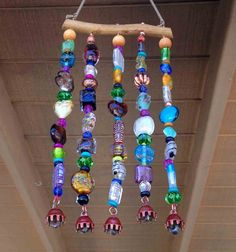 "Windchime/suncatcher. Mesquite wood and nylon string, beads and bells. Measures 4 1/2"" wide X 9"" in length. Waxed cotton cord for hanging adds 5 1/2 inches to total length. $25."