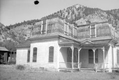 Lake City Colorado. Senate Saloon, billiard hall, bowling alley, livery stable and, in 1929, the Vickers Dude Ranch. This 1942 print shows the L-plan house in disrepair, corner porch with missing balusters and spindles along porch frieze, a projecting three-sided bay, and boarded-up windows and doors.