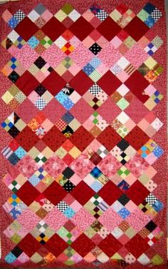 Scrappy Four Patch: I think the alternation of rows of the reds and pinks in the non-pieced patches brings a lot of interest to this charity quilt--inspiration for quickly piecing a quilt for charity--