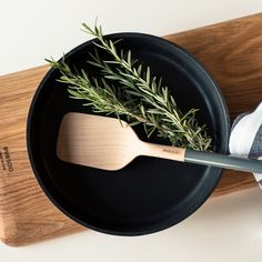 Product styling and photography of Eva Solo - Nordic Kitchen frying pan and wooden spatula for Coolfoodstuff, styled with rosemary, tea towel and Eva Solo cutting board