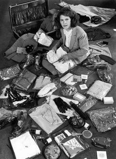 Photographer Margret Bourke-White sitting amidst contents of opened suitcase, US 1942 by Alfred Eisenstaedt