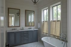 source: Geoff Chick  Beautiful bathroom with shiplap paneled walls over a carrera marble mosaic tiled floor. The bathroom features a pair of wood framed mirrors over a dual gray vanity with louvered cabinet doors paired with white hardware alongside undermount sinks framed by a marble countertop. Freestanding tub with a traditional style faucet sits under windows covered in linen grommet cafe curtains.