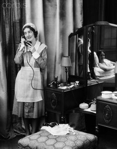 1920s 1930s maid in uniform talks on telephone in front of vanity dressing table other woman is seen as reflection in mirror