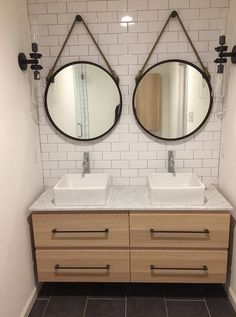 """""""After"""" photos of 10th flip - It's Great to Be Home. Master bathroom with floating Ikea Godmorgon vanity in white oak finish, gray porcelain tile floor, black hardware, round captain mirrors, vessel sinks, modern rustic, subway tile with gray grout"""