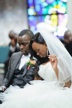 The bride and groom bow their heads in prayer.