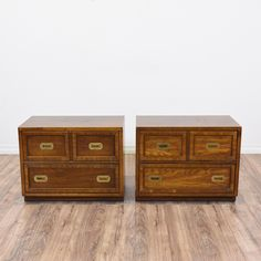 This pair of campaign style nightstands are featured in a solid wood with a gorgeous glossy light walnut finish. These end tables are in great condition with 2 large drawers, a bottom toe kick and shiny brass hardware. Eye catching bed side tables with storage! #contemporary #dressers #nightstand #sandiegovintage #vintagefurniture