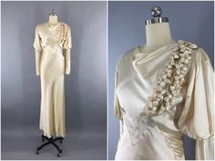 Stunning vintage 1930s wedding dress. Originally worn in 1935. Light champagne bias cut rayon duchesse satin with cowl neckline and full leg o'mutton sleeves. Attached satin half-belt in back with silver-tone buckle encrusted in faux pearls. Lovely satin flowers down the left side of the bodice. Snaps up the left side.  It is in good condition, there is little wear to the satin in under one arm at a pointed seam, and the buckle is missing a couple pearls. There are a couple specks on the...