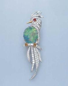 AN ATTRACTIVE OPAL AND DIAMOND BIRD OF PARADISE BROOCH, BY CARTIER  The oval black opal body to the pavé-set diamond bird with ruby eye perched on a baguette-cut diamond branch