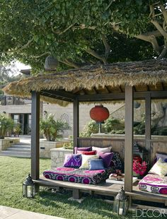 A Balinese-style pavilion topped with woven sea grass holds beds covered in vintage suzanis from Turkey and pillows in outdoor prints by Martyn Lawrence Bullard Fabrics; the lanterns are from Design Mix Furniture.