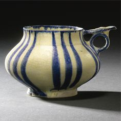 A FINE INTACT KASHAN UNDERGLAZE-DECORATED HANDLED CUP, PERSIA, CIRCA 1200-1220 the frit body of compressed globular form on a short vertical foot with ring handle and foliate thumb-piece, painted in underglaze cobalt blue on a white ground with vertical stripes running the height of the body and around the edge of the rim and handle Islamic World, Islamic Art, Pottery Mugs, Ceramic Pottery, Art Nouveau, Teapots And Cups, China, Ceramic Cups, White Ceramics