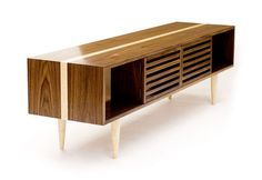This media console is the latest addition to our Bucks collection of tables. Long and sleek, the console is made entirely from solid wood. The cabinet uses miter joints to let the contrasting stripe flow around the sides and through the sections of the table uninterrupted. In addition to the open sections on the ends, the central part of the console has two slatted doors which conceal electronics while allowing for remote control operation. A matching adjustable interior shelf provides space…